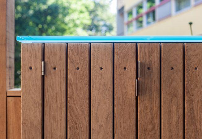 Twee eikenhouten bergkasten aan weerszijde van het einde van de veranda bieden ruimte aan technische voorzieningen en opbergruimte